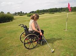 Photo d'une jeune femme en fauteuil qui joue au swin golf